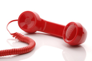 Red old fashioned telephone handset isolated on a white concept for urgent or important customer sup